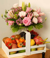 Pink Roses, Pink Lily And Wax Flowers With A Tray Of Assorted Fruits
