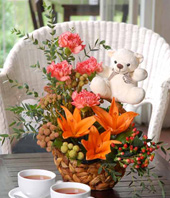 Orange Lilies With Carnations, And Other Flowers In A Basket With White Bear