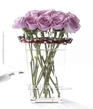 12 purple roses with a glass vase