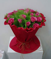 A bouquet of 19 pink roses with green foliages