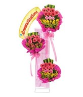 Tall standing arrangement of pink roses, pink gerberas & others
