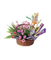 Assorted cadies and pink roses arrangement in a basket