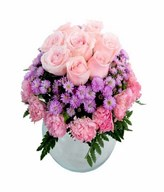 Soft pink roses and pink carnation with purple flower and leave in glass vase