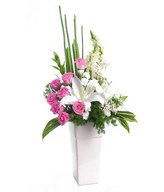 Arrangement of pink rose, white lily, white carnation and white snap dragon in vase