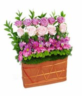 Arrangement of soft pink and Purple roses with mixed carnatin and green puma in basket