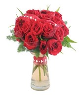 Exquisite floral arrangement in a original vase with vibrant red roses