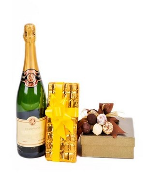A bottle of champagne with 2 boxes of chocolates