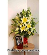 Creme lilies with white eustoma and yellow phoenix in long glass vase filled with vibrant red chilli