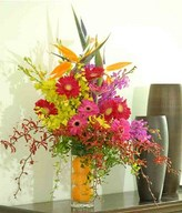 Bird Of Paradise, Pink Gerberas With mixed colour of Orchids In Glass Vase Filled With Orange