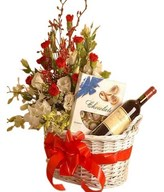 A basket of red wine, a box of chocolate, and bouquet of red & white carnations