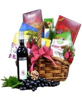 Red wine with assorted chocolates, cookies and snacks in a basket