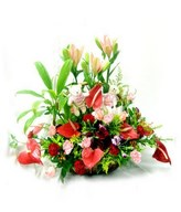 Basket of colorful lilies, carnations, and anthuriums.