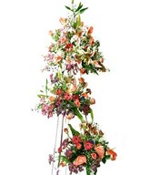 Stand arrangement of carnations, daisies, stargazers, orchids, and lush of greens