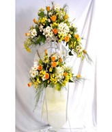 Standing flower arrangement of orange roses and daisies