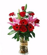 Scarlet gerberas and pink lilies in a hand bouquet